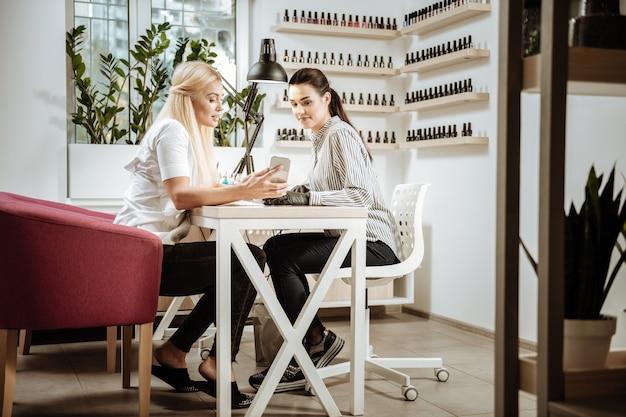 Mostrando foto. mulher de negócios loira mostrando foto da arte de unhas de seu mestre de manicure