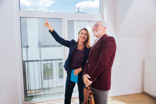 Mostrando janela. corretora de imóveis loira usando uma blusa elegante e elegante mostrando uma bela janela em uma casa moderna