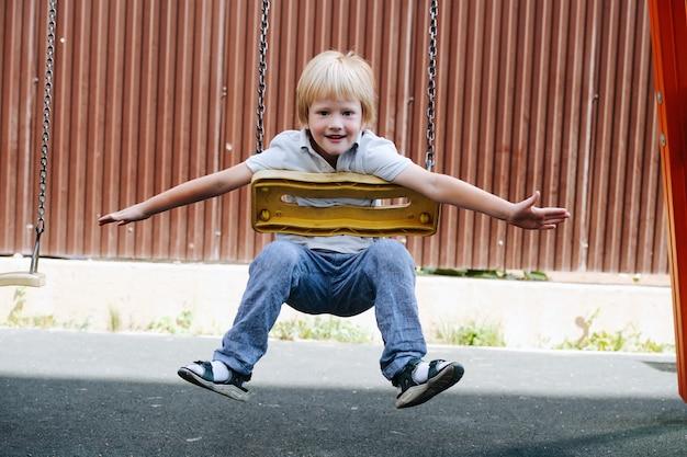 Mostrando o garotinho andando em balanços de barriga em um parquinho infantil. ele está olhando para a câmera, abra os braços para demonstrar que está no controle.