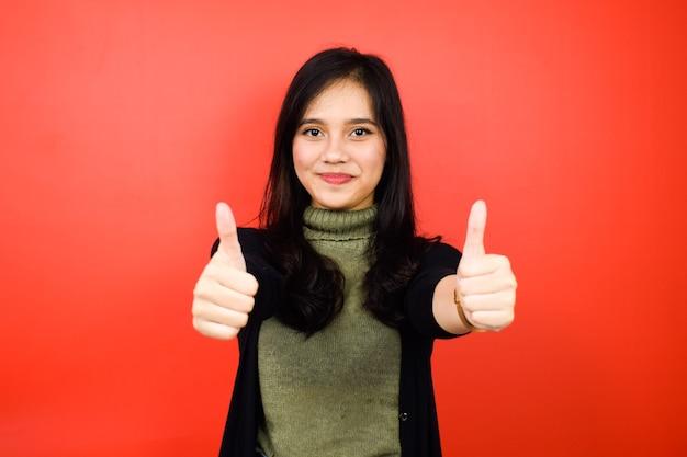 Mostrando o polegar para cima aprovar sinal de jovens lindas mulheres asiáticas usando suéter preto isolado no vermelho