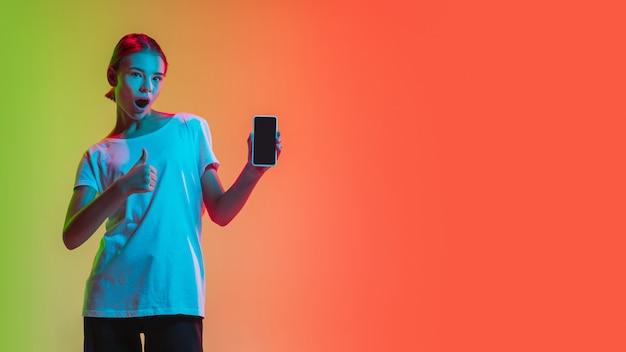 Mostrando o retrato de uma jovem garota caucasiana em um estúdio gradiente verde laranja