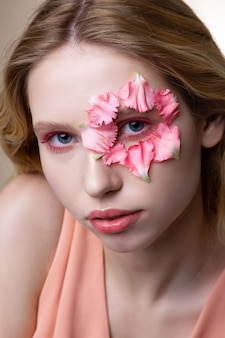 Mostrando pétalas. modelo de olhos azuis com visuais rosa mostrando pequenas pétalas de rosa no rosto enquanto posa