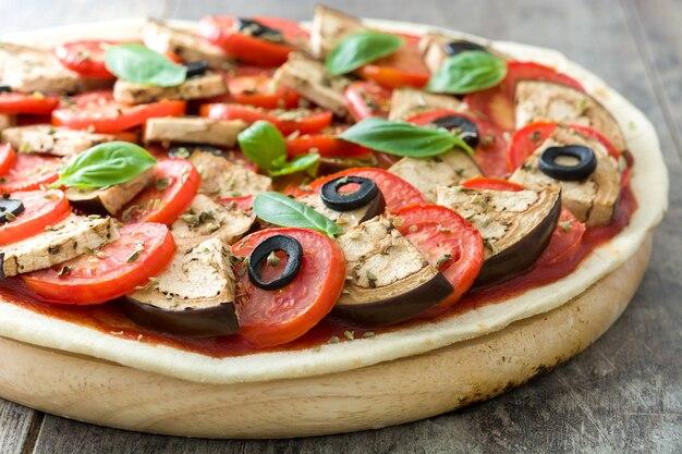 Mostrando pizza vegetariana com berinjela, tomate, azeitonas pretas, orégano e manjericão na mesa de madeira