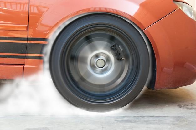 Mostrando pneus queimando carro de corrida na pista.