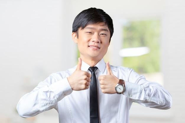 Mostrando, polegares, jovem, asiático, homem negócio
