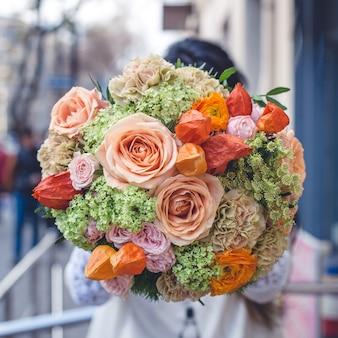 Mostrando um buquê de flores mistas na rua.