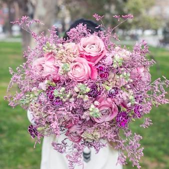Mostrando um buquê roxo de flores no jardim
