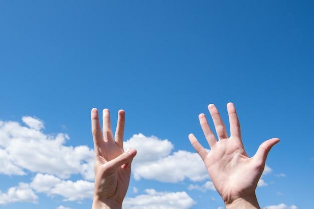 Mostrando um close da mão de uma mulher mostrando uma palma aberta e três dedos isolados em um fundo de céu azul com nuvens, o número oito é o símbolo da linguagem de sinais