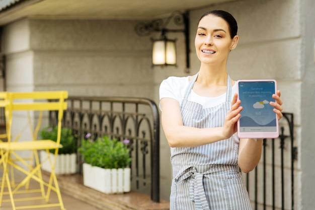 Mostrando um tablet. garçonete confiante e progressiva sorrindo e se sentindo feliz enquanto segura um aparelho moderno