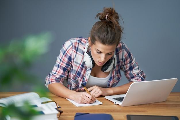 Mostrando uma aluna cansada aprendendo tarde em casa