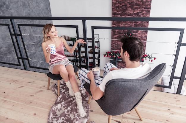 Mostrando uma foto. mulher loira magra de cabelos compridos usando meias grossas brancas mostrando uma foto para o marido