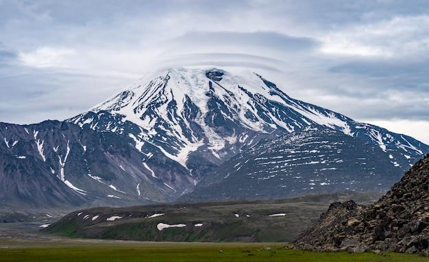 Mostrar vista do vulcão com fundo azul do céu e nuvens