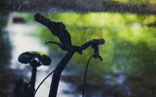 Mostre em silhueta a bicicleta no dia chuvoso com natureza do bokeh e a estrada molhada. conceito triste chuva caindo.
