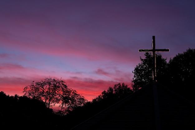Mostre em silhueta a cruz no telhado da igreja com o céu dramático no alvorecer.