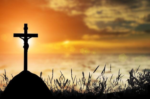 Mostre em silhueta a cruz sobre o fundo borrado do por do sol.
