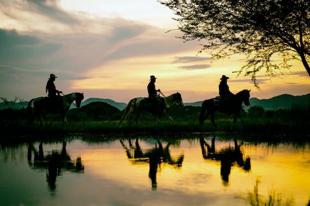 Mostre em silhueta a equitação do vaqueiro em uma montanha com um céu amarelo.