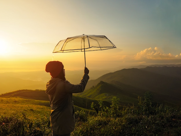 Mostre em silhueta a mão da mulher que guarda o guarda-chuva na montanha no nascer do sol.