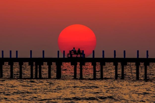 Mostre em silhueta a noite na praia céu laranja de verão Foto Premium