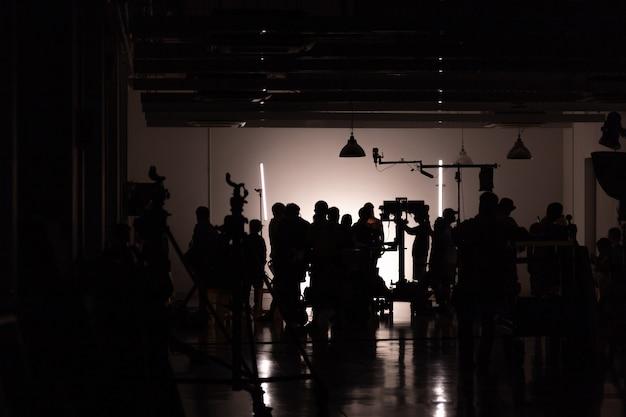 Mostre em silhueta imagens da produção de vídeo nos bastidores, equipe lightman e cameraman trabalhando em conjunto com o diretor no estúdio