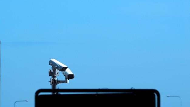 Mostre em silhueta imagens de câmeras de segurança ou vigilância por vídeo cctv ao ar livre, que é um sistema de tecnologia