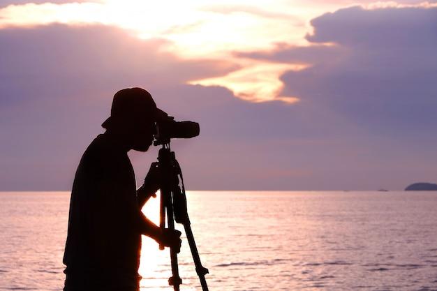 Mostre em silhueta o fotógrafo que toma a foto da luz do por do sol com o tripé no mar em tailândia. o céu tem tom de cor roxo e rosa.