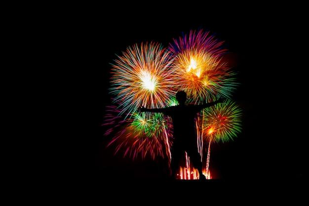 Mostre em silhueta o homem bem sucedido no pico, lindos fogos de artifício coloridos na praia do mar.