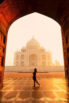 Mostre em silhueta o turista não identificado da mulher que anda perto de taj mahal em agra india.