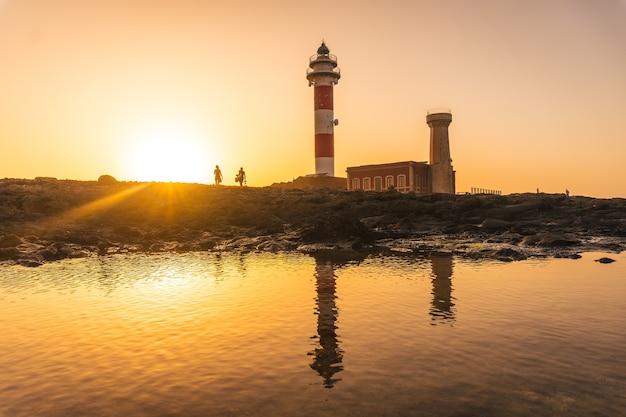 Mostre em silhueta um casal no pôr do sol no farol de toston, punta ballena, perto da cidade de el cotillo, ilha de fuerteventura, ilhas canárias. espanha