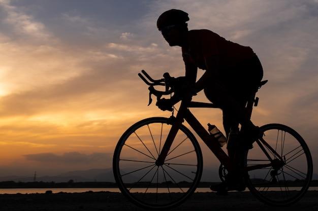 Mostre em silhueta um homem ciclista de bicicleta de estrada, pedalando pela manhã.
