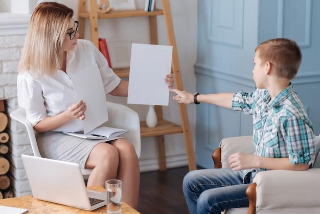 Mostre-me. mulher jovem e atraente usando roupas elegantes, segurando duas folhas de papel nas mãos, sentada em posição semi-aberta