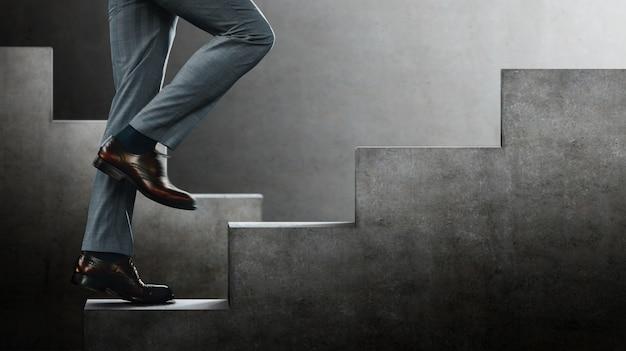 Motivação e conceito desafiador. passos para o sucesso. seção inferior do empresário subindo na escada. lugar sureal