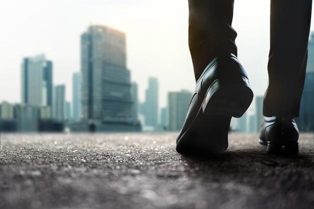 Motivação, passos em frente para um conceito de sucesso. desafiante nos negócios e na carreira. seção baixa do empresário andando na rua para a cidade.