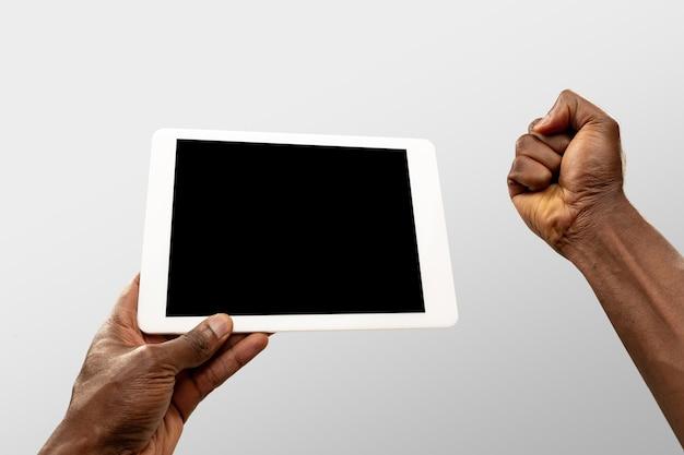 Motivação, punho. feche as mãos masculinas segurando um tablet com tela em branco durante a exibição on-line de jogos de esporte popular, campeonatos. copyspace para anúncio. dispositivos, gadgets, conceito de tecnologias.