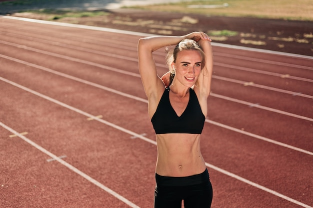 Motivado cabe mulher no sportswear fazendo aquecimento das mãos antes de correr na pista do estádio em dia ensolarado