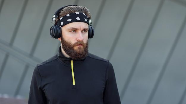 Motivado para o treino intenso, ouvindo música com fones de ouvido, o homem de treinamento mostra por