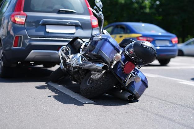 Moto azul deitada na estrada perto do carro.