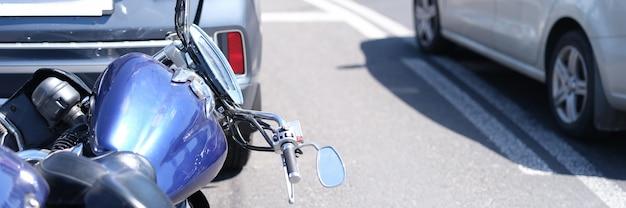 Moto azul deitada na frente do carro na estrada, close-up