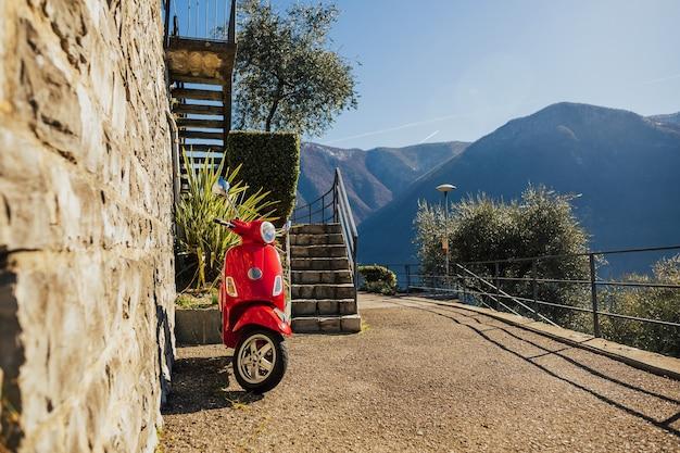 Moto ed em pé na estrada com montanha