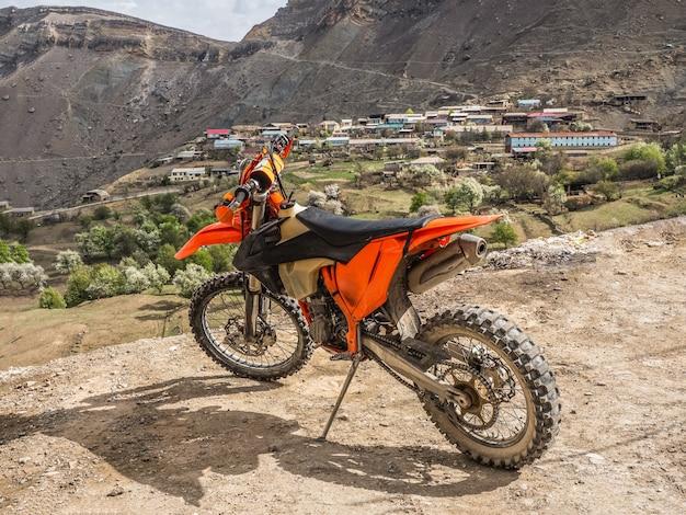 Moto laranja em um penhasco no fundo de uma aldeia de montanha e altas montanhas. conceito de viagens.