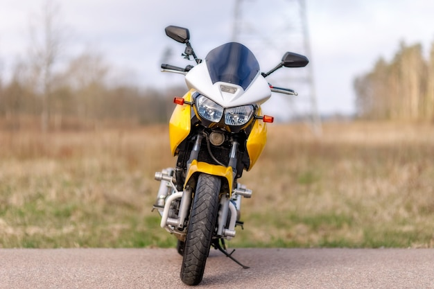 Moto parada na lateral de uma estrada amarela, vista frontal
