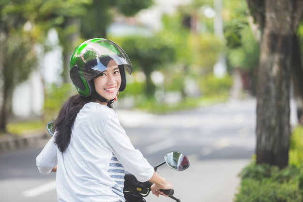 Motocicleta bonita da equitação da mulher
