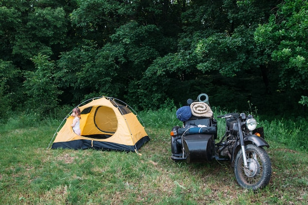 Motocicleta com carro lateral estacionada perto da barraca na floresta