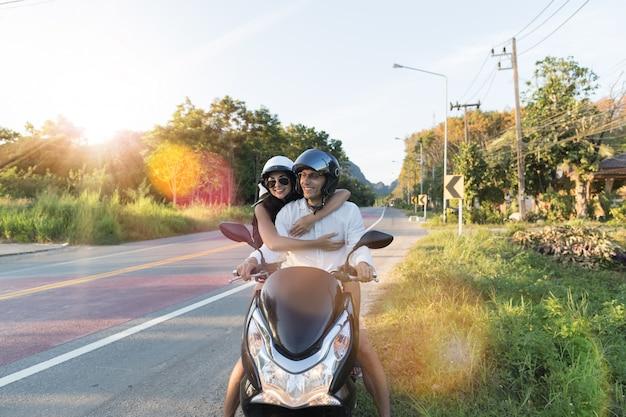 Motocicleta de equitação de casal feliz no campo excited mulher e homem viajam na viagem de moto
