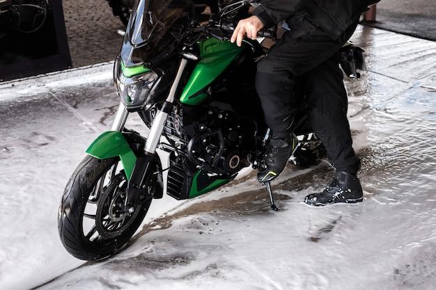 Motocicleta e motoqueiro na lavagem de carros em espuma