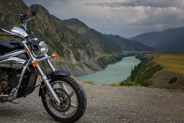 Motocicleta e rio de montanha com pedras