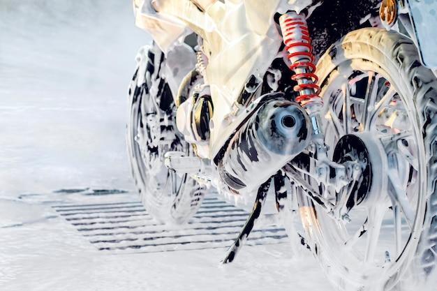 Motocicleta em espuma automotiva na lavagem de carros self-service