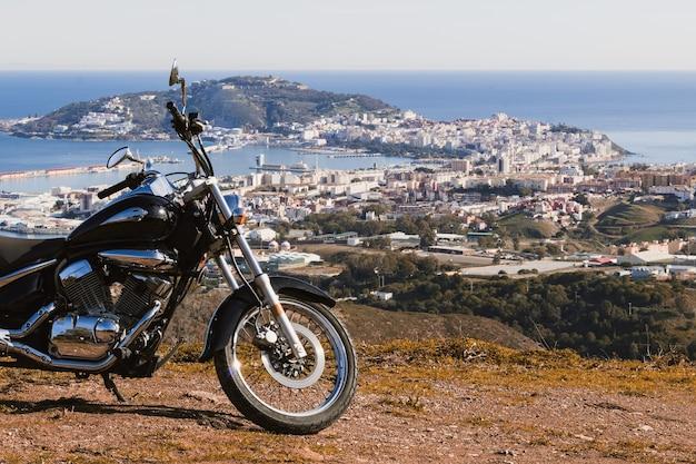 Motocicleta personalizada com a paisagem de uma cidade marítima ao fundo