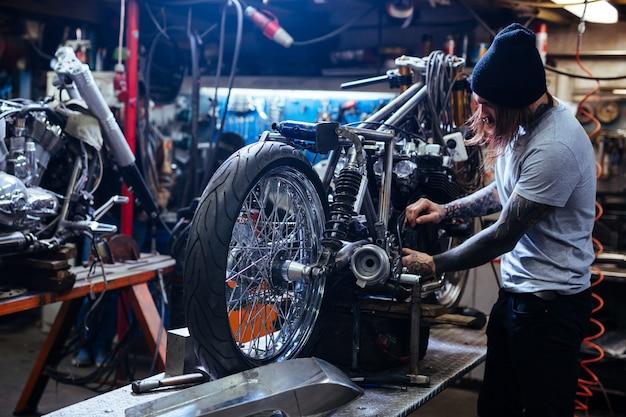 Motocicleta tatuagem reparando motocicleta em oficina