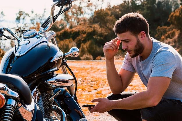 Motociclista agachado preocupado com uma quebra de motocicleta
