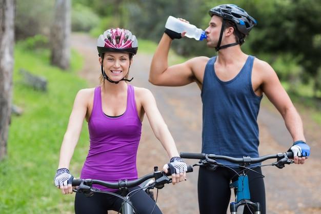 Motociclista água potável por mulher na floresta